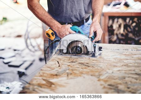 Construction Man Working With A Chop Saw In Wood Workshop. Details Of Wood Cutting Using Circular Sa