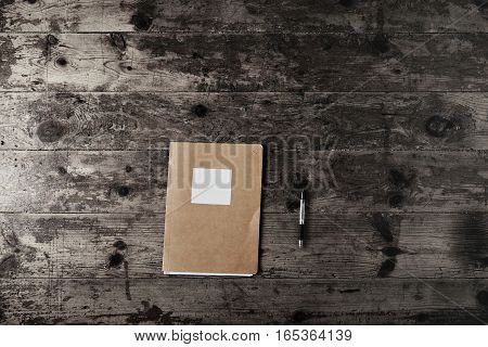 Simple notebook with craft paper cover and empty white label and a black ballpoint pen on a gray wooden table