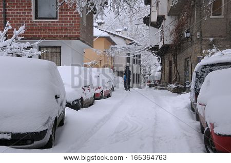 VELIKO TARNOVO BULGARIA - JANUARY 6 2017: Clearing snow from the car roof in General Gurko street on the winter day