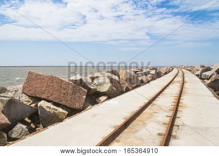 rail over breakwater at cassino beach and blue sky