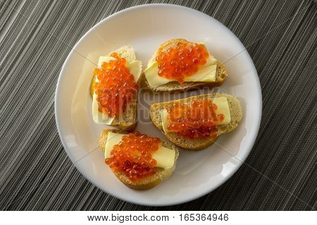Red caviar on bread and butter closeup four sandwiches on white plate. View from above