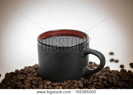 Black coffee cup on coffee beans close-up
