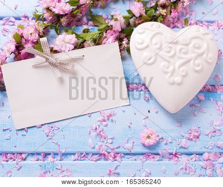 Background with elegant sakura flowers white decorative heart and empty tag on blue wooden planks. Selective focus. Place for text.