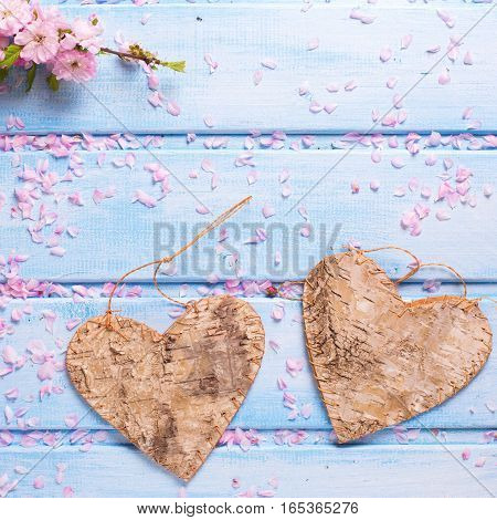 Valentine Day concept. Two decorative hearts and pink sakura flowers on blue wooden background. Selective focus. Place for text. Square image.