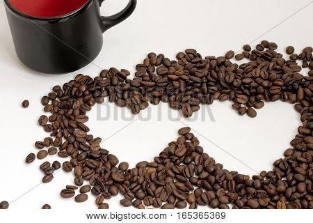 Two hearts of coffee beans with a cup of black on white