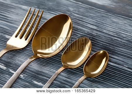 Gold spoons and fork on the gray wooden background. vintage tableware with scratches and scrapes. Soft focus macro.