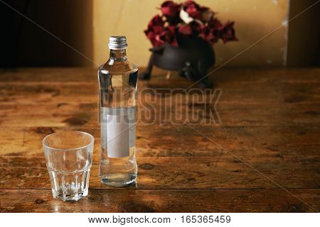 Glass bottle with water and an empty tumbler on a vintage wooden table with paper roses in the background