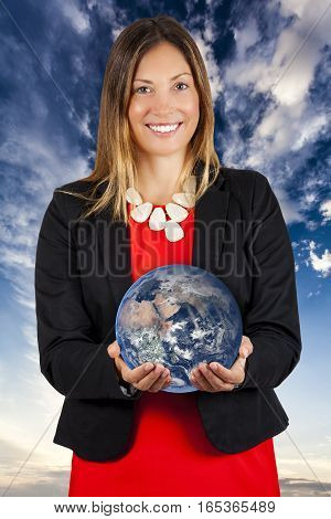 World at your hands. Woman smiling with earth in hands. A young business woman with the world in hands. Sky and clouds in the background. Concept of power in the hands.