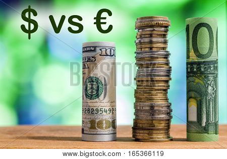 One hundred euro and one hundred US dollar rolled bills banknotes with euro coins and american cents on green blurred bokeh background. Dollar vs Euro concept.
