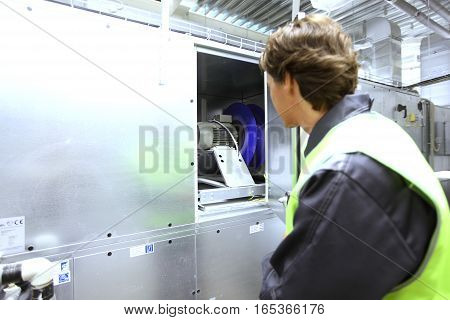Worker in uniform check electrical engine in switchgear room