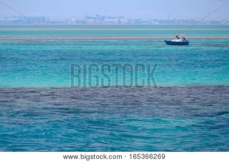Red Sea background, clean blue water, small waves, boat, city skyline, Egypt