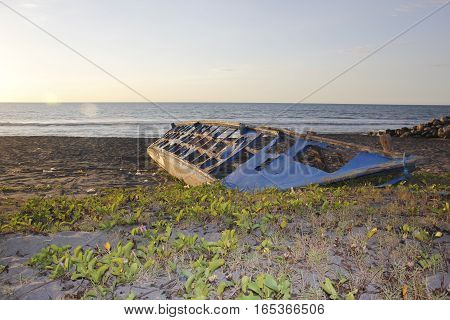 A wreckage of a fishing boat lying on a beach