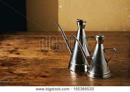 Two shiny steel made vintage and different sized metal olive oil dispensers with long spouts, one next to other, on textured grainy brown table surface