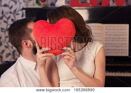Young beautiful couple whispering behind the red heart shaped pillow.