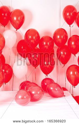 Many red and white baloons on the bed on white background