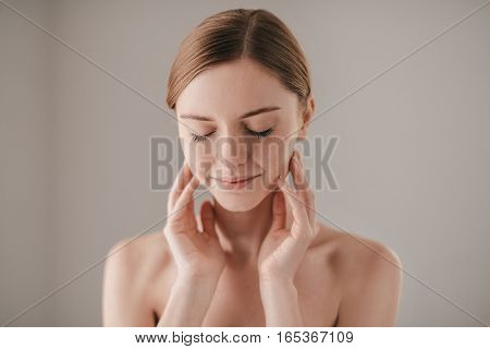 Perfect skin. Portrait of redhead woman with freckles keeping eyes closed and smiling while keeping fingers on her face and standing against grey background