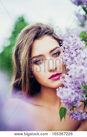 Portrait of young beautiful woman posing among lilac flowers. Professional make-up and hairstyle. Perfect skin. Fashion photo. Natural beauty. Springtime.