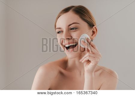 Bringing freshness to her skin. Studio portrait of attractive woman cleansing her skin with a cotton pad while standing against background