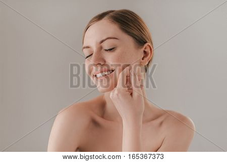 Enjoying her soft skin. Beautiful young woman keeping eyes closed and touching her face while standing against background