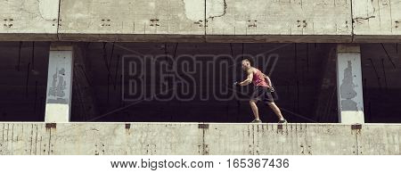 Young athletic built man jogging on the thin deck walls of an abandoned building