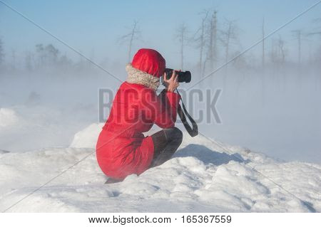 Woman photographer taking pictures during winter blizzard.