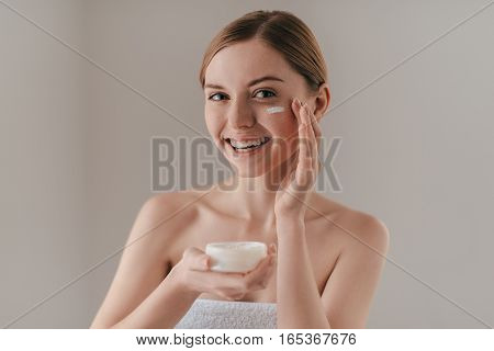 Taking good care of her skin. Attractive young woman looking at camera and smiling while standing against background