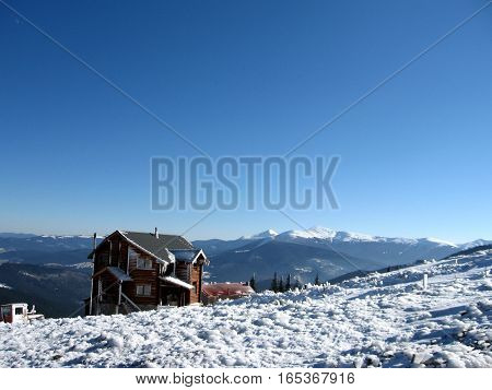 A wooden house in winter mountains covered with snow and ice on a background of snow-capped peaks