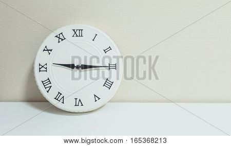 Closeup white clock for decorate show a quarter past nine or 9:15 a.m. on white wood desk and cream wallpaper textured background with copy space