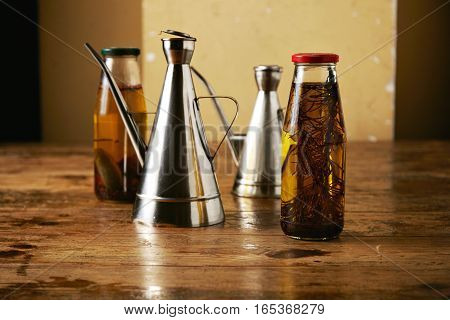 Presentation of two glass bottles with artisan home made spicy olive oil with rosemary and peppers and two shiny metal cruets on a rough brown table.