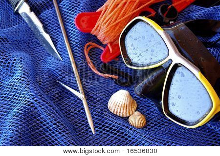 Details of scuba-diving and spear-fishing gear over a blue fishing net bag