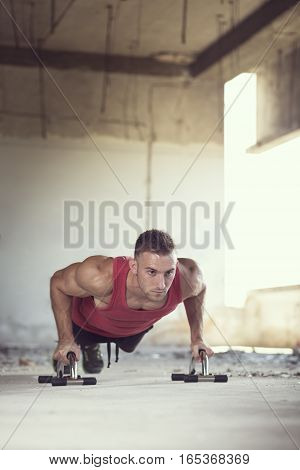 Muscular athletic built young man doing a series of push ups in a ruin building before workout