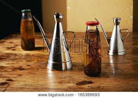 Rough rustic wooden table with two bottles of flavored olive oil and two stainless steel cruets against beige wall background