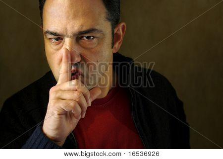 Man holding a finger on his mouth demanding silence.