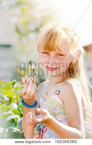 Young girl illuminated by the sun - smiling and eating strawberries