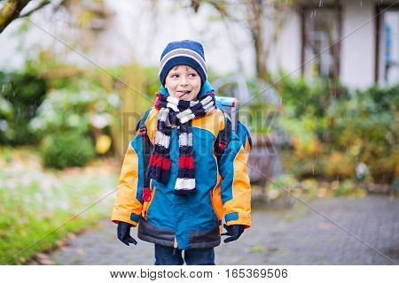 Little school kid boy of elementary class walking to school during snowfall. Happy child having fun and playing with first snow. Student with backpack in colorful winter clothes catching snowflakes.