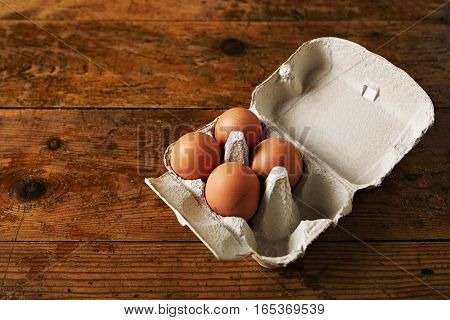 Open egg carton for six eggs containing four brown eggs on a rough rustic brown wooden table