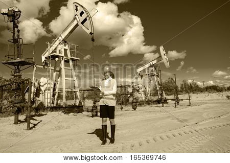 Woman engineer in glasses on the oil field wearing helmet and work clothes. Industrial site background. Oil and gas concept. Toned sepia.