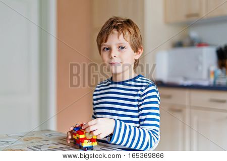 Little blond school kid boy playing with lots of small colorful plastic blocks indoor. child wearing colorful shirt , having fun with building and creating. Active leisure for children