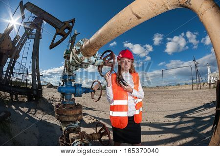 Woman engineer in the oil field talking on the radio wearing red helmet and orange work clothes. Industrial site background. Oil and gas concept.
