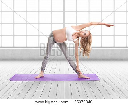 Full Body Portrait Of Pregnant Woman Doing Yoga On a Purple Exercise Mat in front of a large window