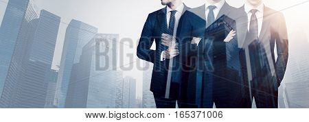 Group of three young businessman wearing suits and posing against backdrop of the modern city.Concept of successful business.Double exposure, skyscraper building at blurred background.Horizontal wide