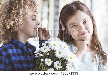 Boy Whispering To Girl's Ear