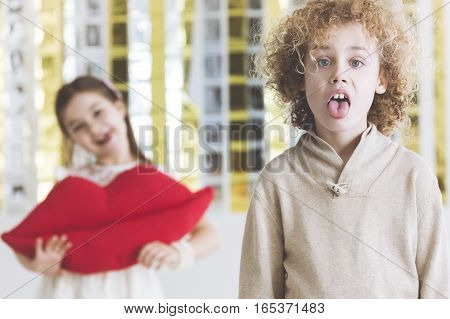 Little disgusted boy and girl holding lips pillow