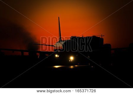 Passenger plane on sunrise or sunset is preparing for taking off from the runway in the airport