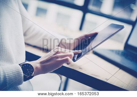 Closeup view of female hand touching button on digital tablet at the wooden desk.Concept young business people using mobile gadgets.Horizontal, blurred background.Film effect