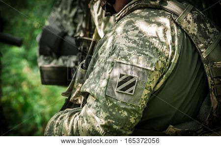 US Army Soldiers on patrol mission in the woodland. Old color film stylization
