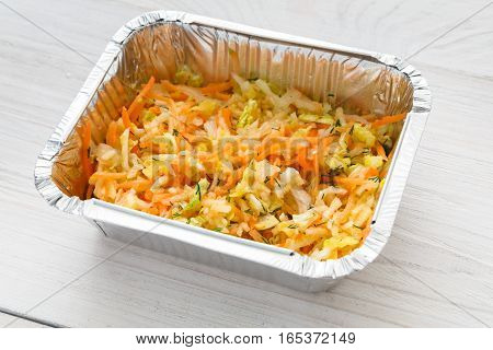 Healthy food in foil box closeup, celery, apple and carrot salad on white wood. Restaurant dishes delivery, lunch for diet