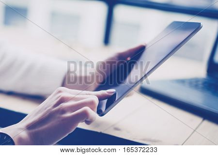 Closeup view of female hand touching screen digital tablet at the wooden table.Concept young business people using mobile devices.Horizontal, blurred background.Film effect