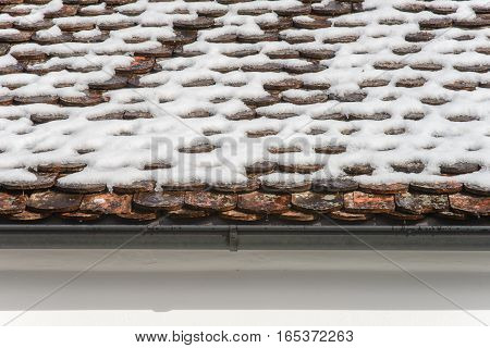 Close-up of a gutter at a roof. snow on roof