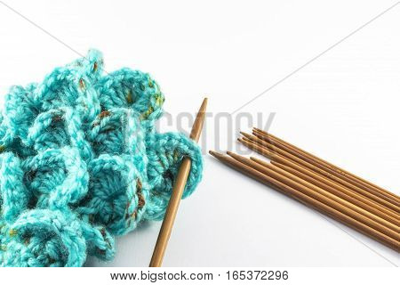Crochet hook and wool on white background